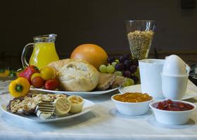 Foto Frühstücksplatte mit Brötchen,Wurst, Ei, Marmelade, Obst, Saft, Kaffee uvw.